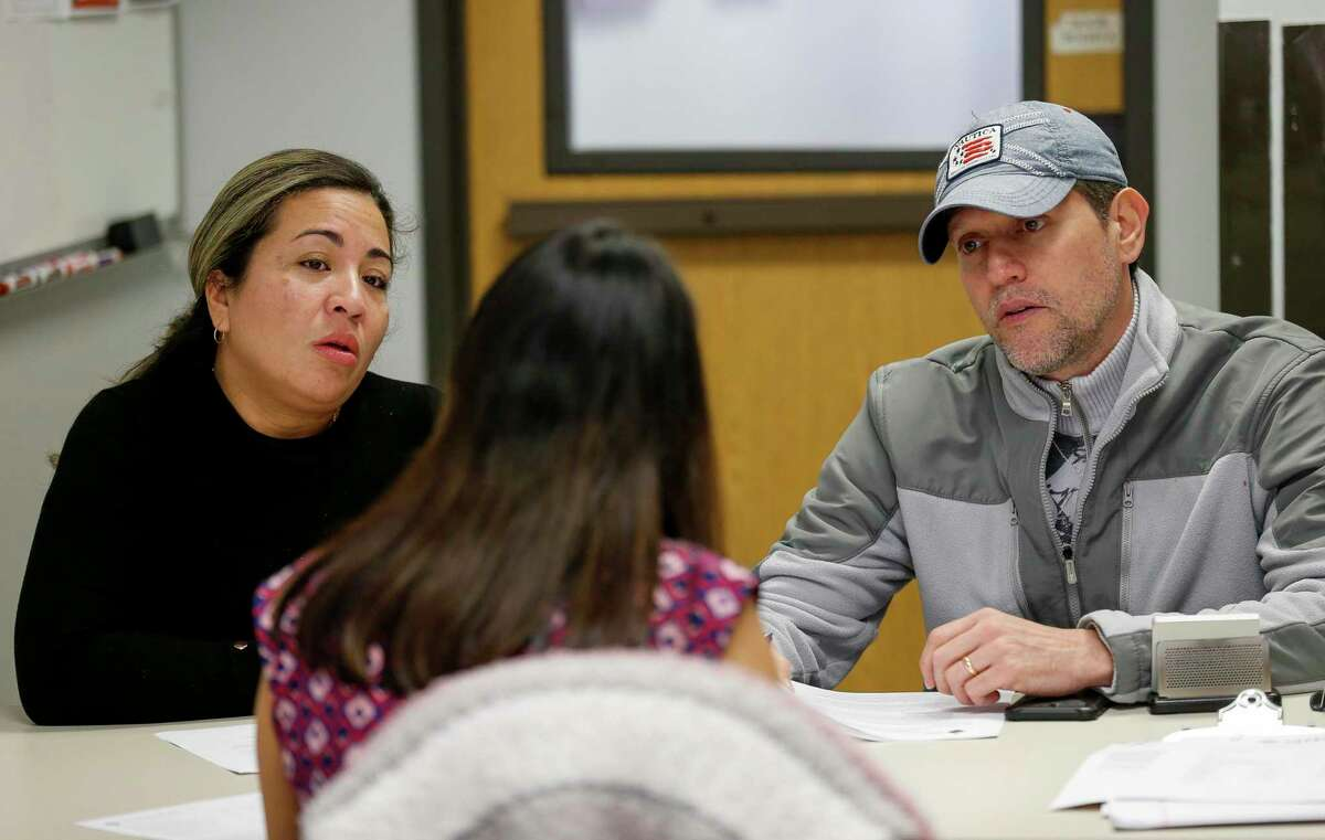 Carmen, left, and her husband George Ospina, right, talk with Noemi Flores, financial counselor with the Financial Empowerment Center of Houston, to come up with a strategy to battle their debt and other financial struggles Friday, Jan. 31, 2020, in Houston. The Financial Empowerment Centers of Houston are set up to help people fix their financial situation, and it's a free service paid for by a grant to the City of Houston.
