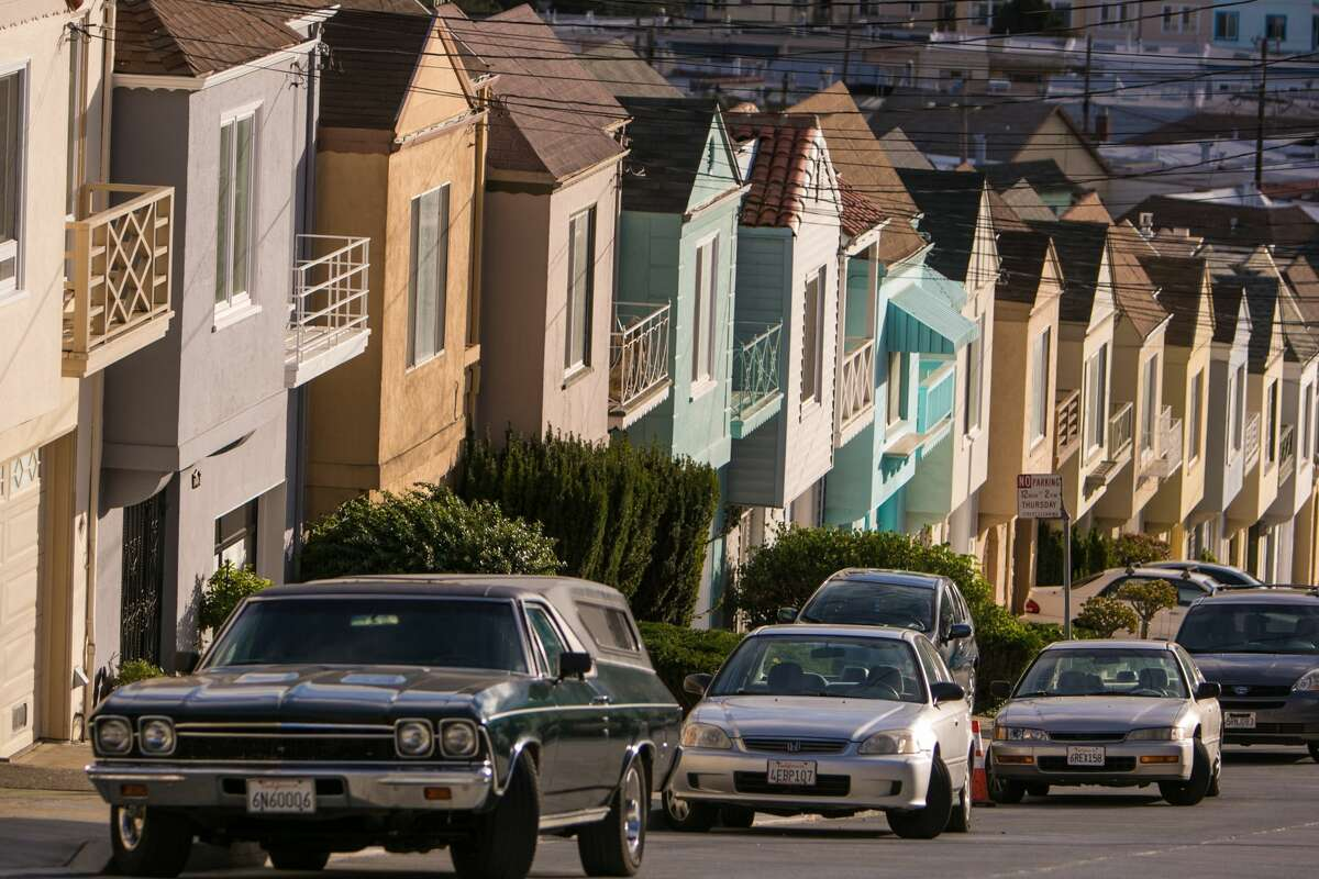 Cars are parked along a row of houses on Potrero Hill. San Francisco's streets are full of themed and patterned thoroughfares.