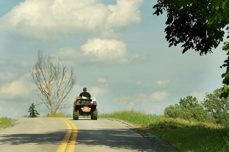Brian Grubb of Bison Island brings food to his bison on his ATV Monday, July 29, 2019 in Sharon Springs, N.Y. Photo: Lori Van Buren / Albany Times Union / 40047563A