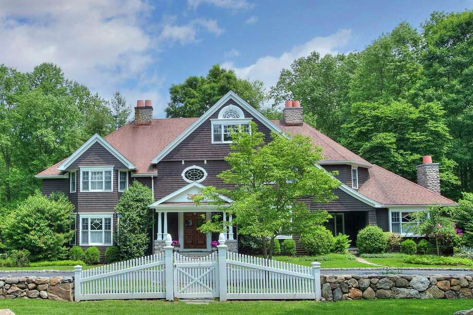 The chocolate brown shingle colonial house at 68 Bayberry Lane sits on a level corner lot just over one acre.