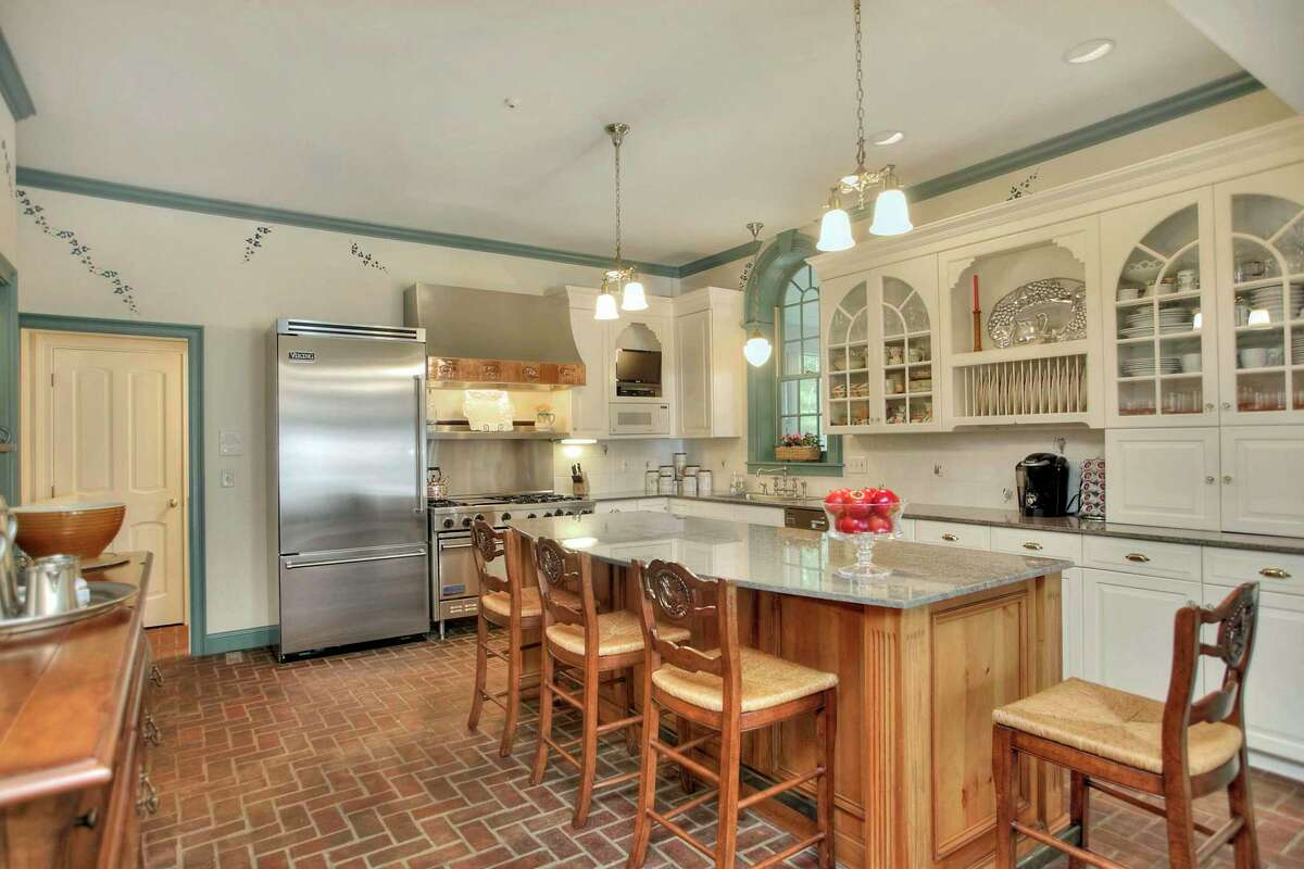 In the spacious gourmet kitchen there is a brick floor, center island/breakfast bar, granite countertops, an open dish rack, glass-front cabinetry, and high-end stainless steel appliances.