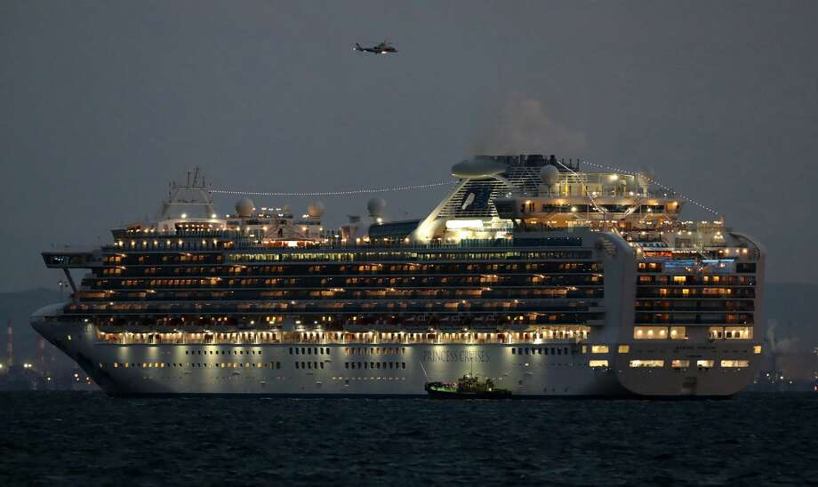 A small boat is pictured next to the Diamond Princess cruise ship with over 3,000 people as it sits anchored in quarantine off the port of Yokohama on February 4, 2020, a day after it arrived with passengers feeling ill. - Japan has quarantined the cruise ship carrying 3,711 people and was testing those onboard for the new coronavirus on February 4 after a passenger who departed in Hong Kong tested positive for the virus. Photo: STR/JIJI PRESS/AFP Via Getty Images