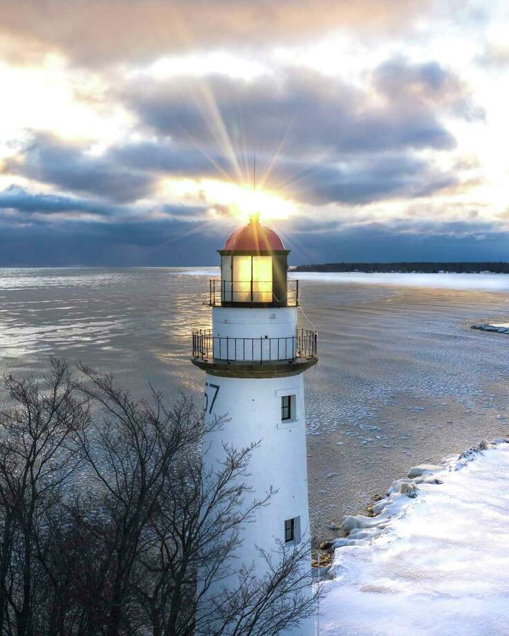 The sun pokes through the clouds, lighting up the Pointe Aux Barques Lighthouse recently. (Tyler Leipprandt/Michigan Sky Media)