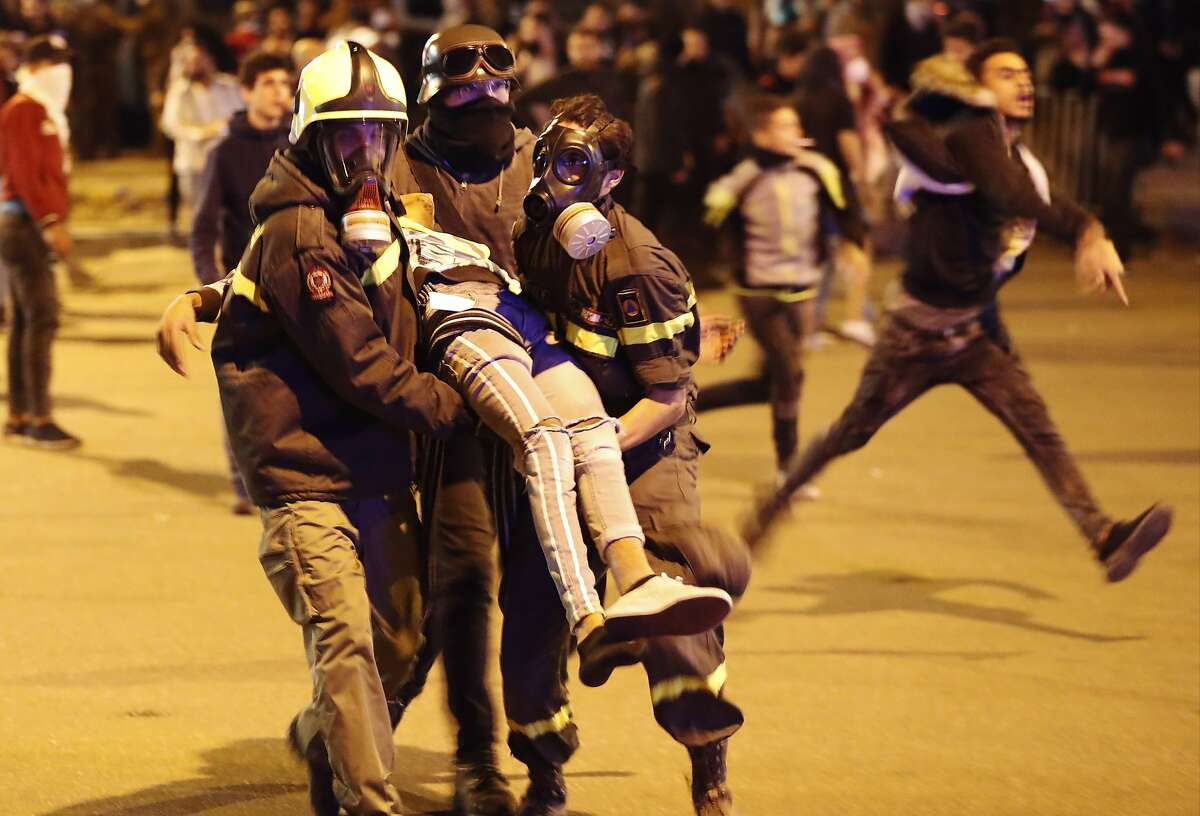 FILE - In this December 14, 2019 file photo, Civil defense workers carry an injured protester after a clash with riot police, in downtown Beirut, Lebanon. Protester's demands for sweeping government reforms won't be squashed easily, even as security forces resort to more violent means of crowd control, such as rubber bullets. Overall, more than 500 people, including over 100 security forces, have been injured last month. (AP Photo/Hussein Malla, File)
