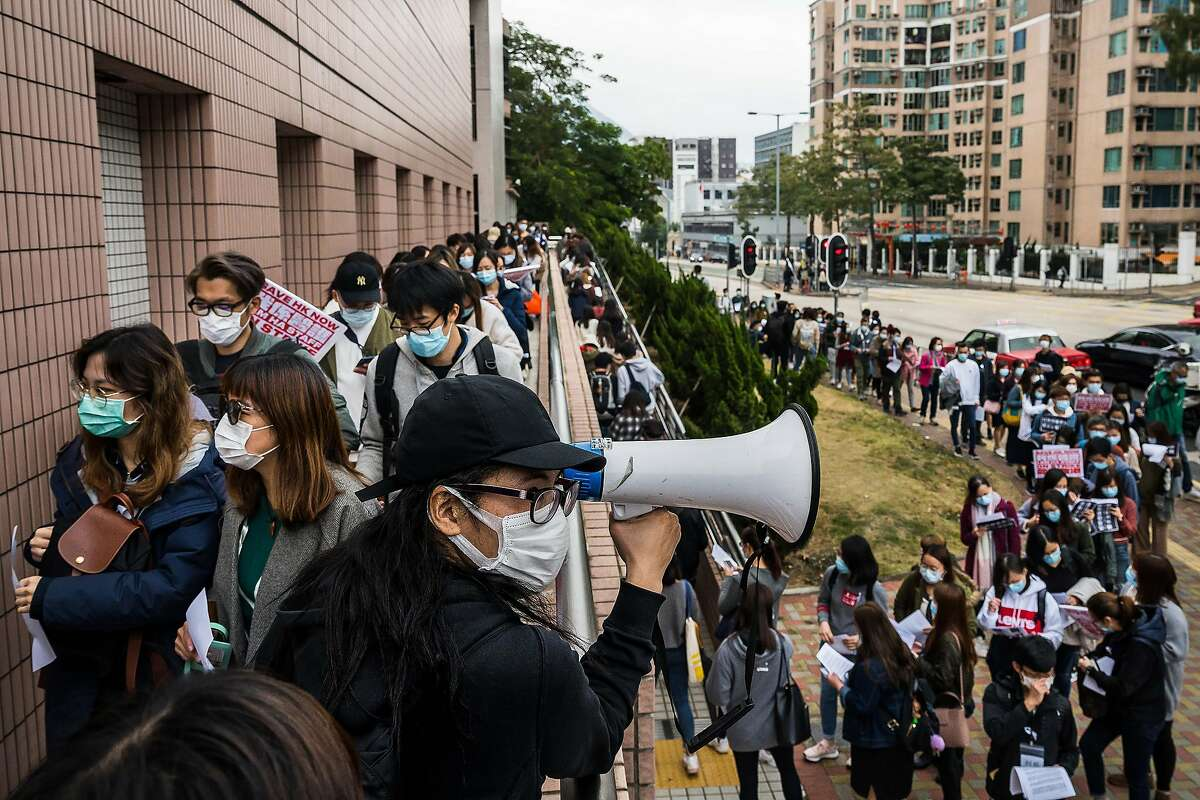 Medical workers in Hong Kong rally Tuesday, Feb. 4, 2020, on the second day of a strike to demand that the government shut the city's border with mainland China. More than 2,500 medical workers went on strike Monday to demand a fully closed border. (Billy H.C. Kwok/The New York Times)