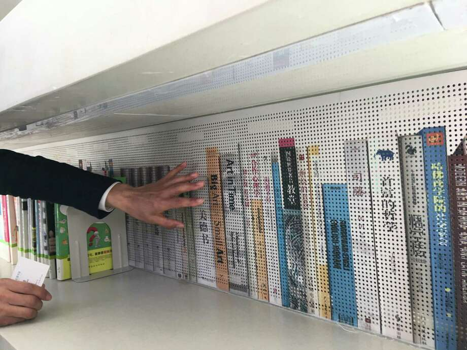 Liu Xiufeng, curator of Tianjin Binhai Library, shows off stacks painted to appear as though they're filled with books at the sprawling library and community complex. Photo: James Osborne, Staff / © 2020 Houston Chronicle
