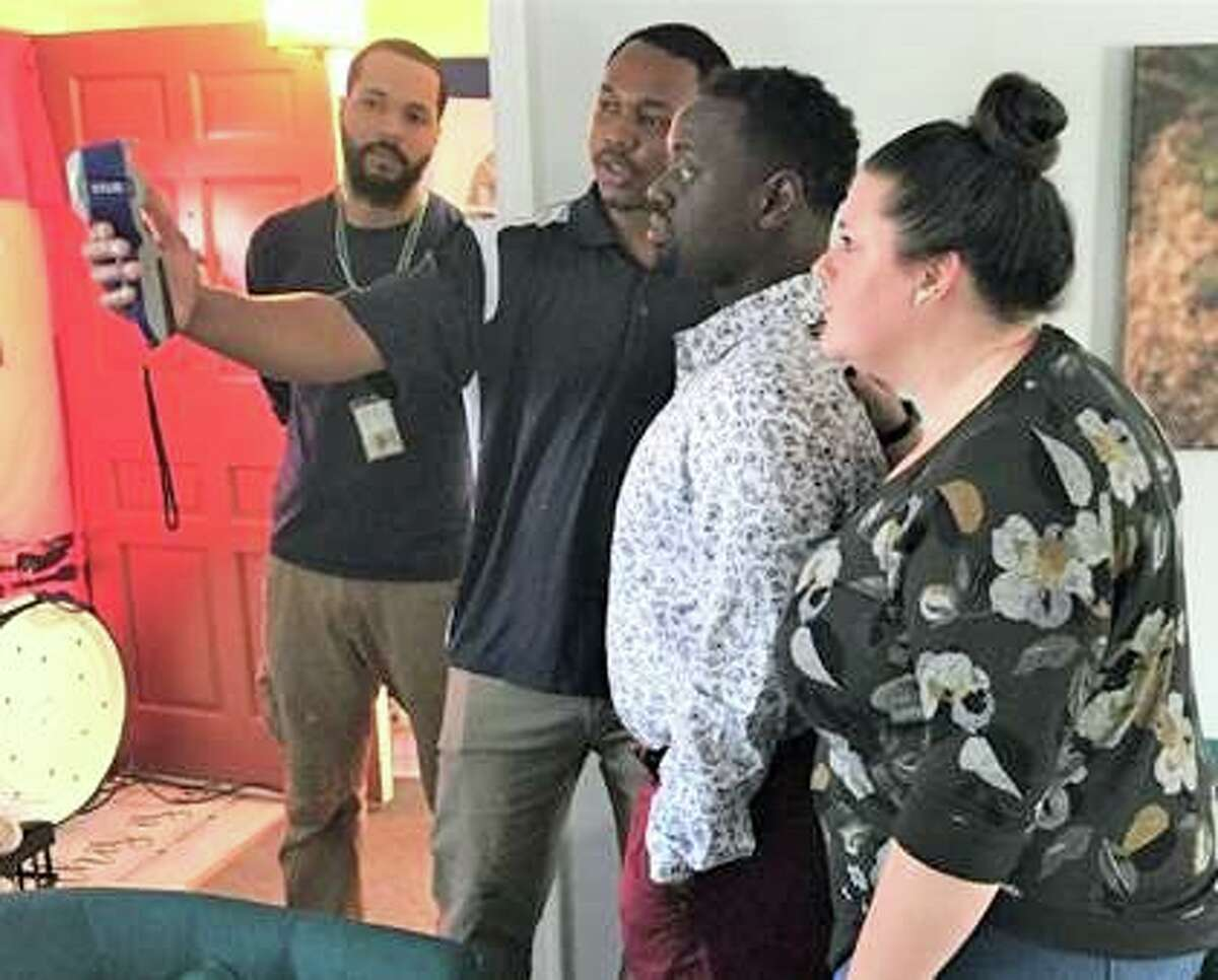 As part of the Home Energy Solutions program, an in-home energy improvement service offered by Eversource, a contractor with CMC-Energy uses a thermal imaging camera to show state Rep. Quentin Phipps, D-Middletown, and his wife Carissa where their home is losing energy.