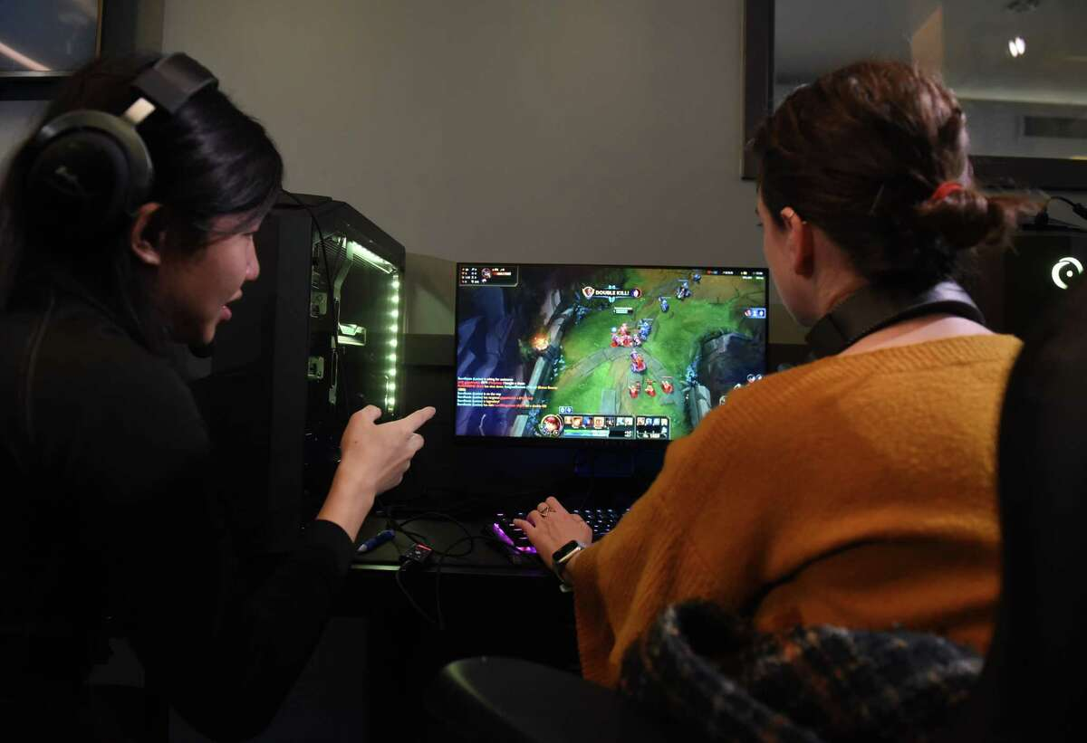 College of Saint Rose Golden Knights varsity e-sports team member, Waixian Tang, left, coaches Times Union reporter Rachel Silberstein, right, in an in-house League of Legends tournament on Tuesday, Feb. 4, 2020, during a media event at Centennial Hall on the Saint Rose campus in Albany, N.Y. (Will Waldron/Times Union)