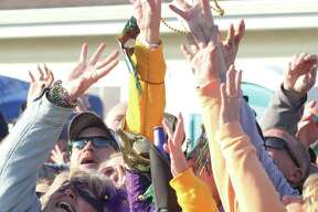 "A group of spectators grab for beads thrown into the crowd during a previous Wordi Gras, a parade held annually in Worden. Organizers tout the event, now 10 years old, as a ""redneck Mardi Gras."""
