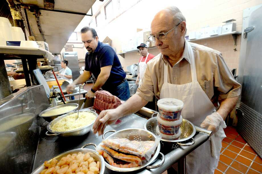 Constantine Megas organizes prepped items as his son Steve unwraps a large cut of beef to slice at The Schooner as they get ready for the opening and first wave of the lunch crowd. The restaurant is among the oldest businesses in the area - one in which Constantine has been working since he was 14 years old when his family immigrated to America from Greece in 1950. Photo taken Tuesday, February 4, 2020 Kim Brent/The Enterprise Photo: Kim Brent/The Enterprise