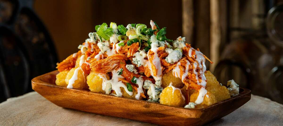 Buffalo Chicken TotsTater tots with buffalo chicken, queso blanco, blue cheese crumbles and green onions.(Available at Bayou City Marketplace Sections 126 and 409)
