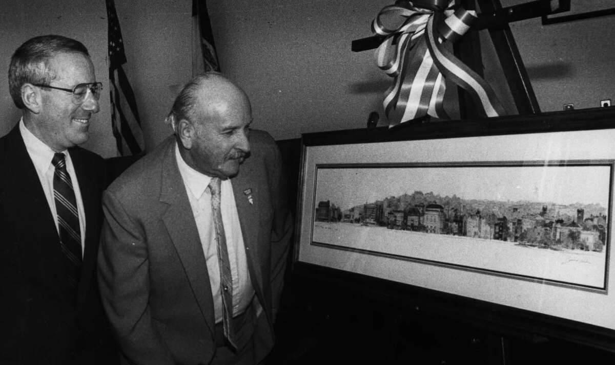 DWORSKY--Troy City Manager, Steve Dworsky, left, and Joseph Salmon, a 39-year employee with the DPW, look over a framed scene of the Troy skyline, given to Salmon's as retirement gift. 4/6/1990. -1- McBride.