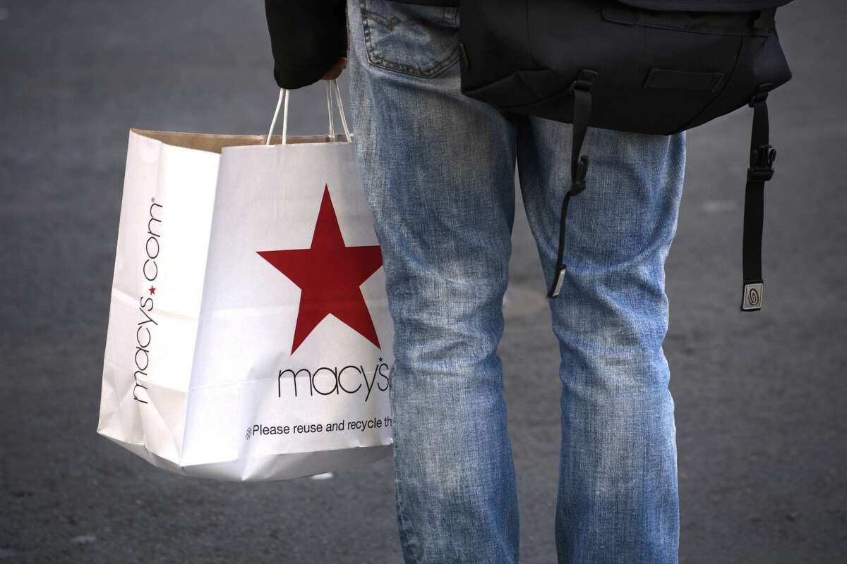 File - A man carrying a Macy's department store shopping bag waits at an intersection in San Francisco. The retailer announced that it will be closing its San Francisco tech offices and 125 of its stores.