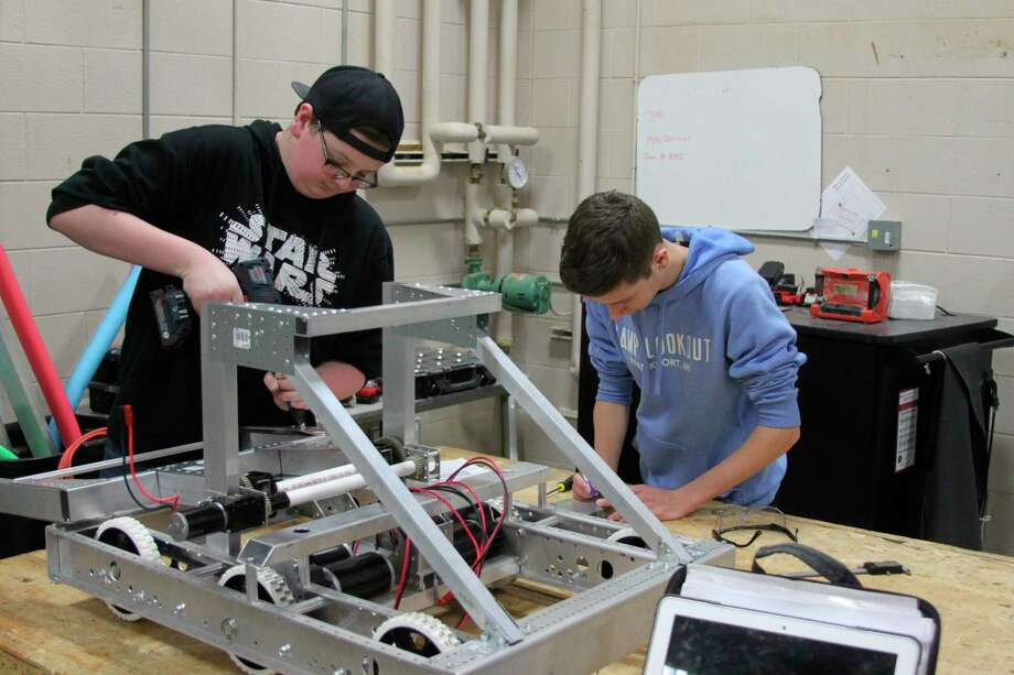 Brandon Sullivan (left) and Luke Herberger (right) work on the Manistee High School Robotics robot. This is the first year the school has had a Robotics team at the high school level and the students are working hard on creating a competitive robot. (Ken Grabowski/News Advocate)