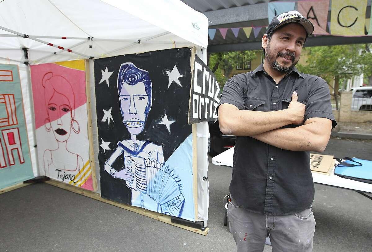 Artist Cruz Ortiz talks about his most recent work during the La Carpa art exhibit during the King William Fair on Saturday, Apr. 26, 2014. (Kin Man Hui/San Antonio Express-News)