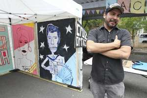 Artist Cruz Ortiz talks about his most recent work during the La Carpa art exhibit during the King William Fair on Saturday, Apr. 26, 2014. (Kin Man Hui/San Antonio Express-News)