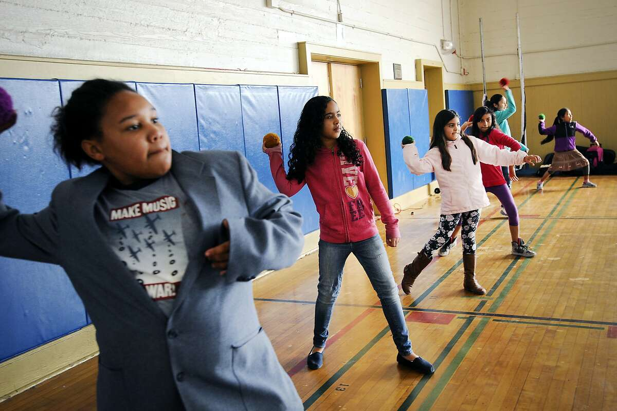 Students of Frank Lara's 4th grade class, including Ruby Penn, left, practice throwing a ball during physical education held in the gymnasium at Buena Vista Horace Mann school in San Francisco, CA, on Thursday, February 12, 2015.