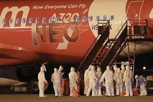 "This handout from the Royal Thai Navy taken and released on February 4, 2020 shows navy officials in protective suits standing beside a plane that brought Thai nationals back from Wuhan, the epicentre of the novel coronavirus outbreak, at U-Tapao Airport in Rayong. (Photo by Handout / various sources / AFP) / -----EDITORS NOTE --- RESTRICTED TO EDITORIAL USE - MANDATORY CREDIT ""AFP PHOTO / ROYAL THAI NAVY "" - NO MARKETING - NO ADVERTISING CAMPAIGNS - DISTRIBUTED AS A SERVICE TO CLIENTS (Photo by HANDOUT/AFP via Getty Images)"