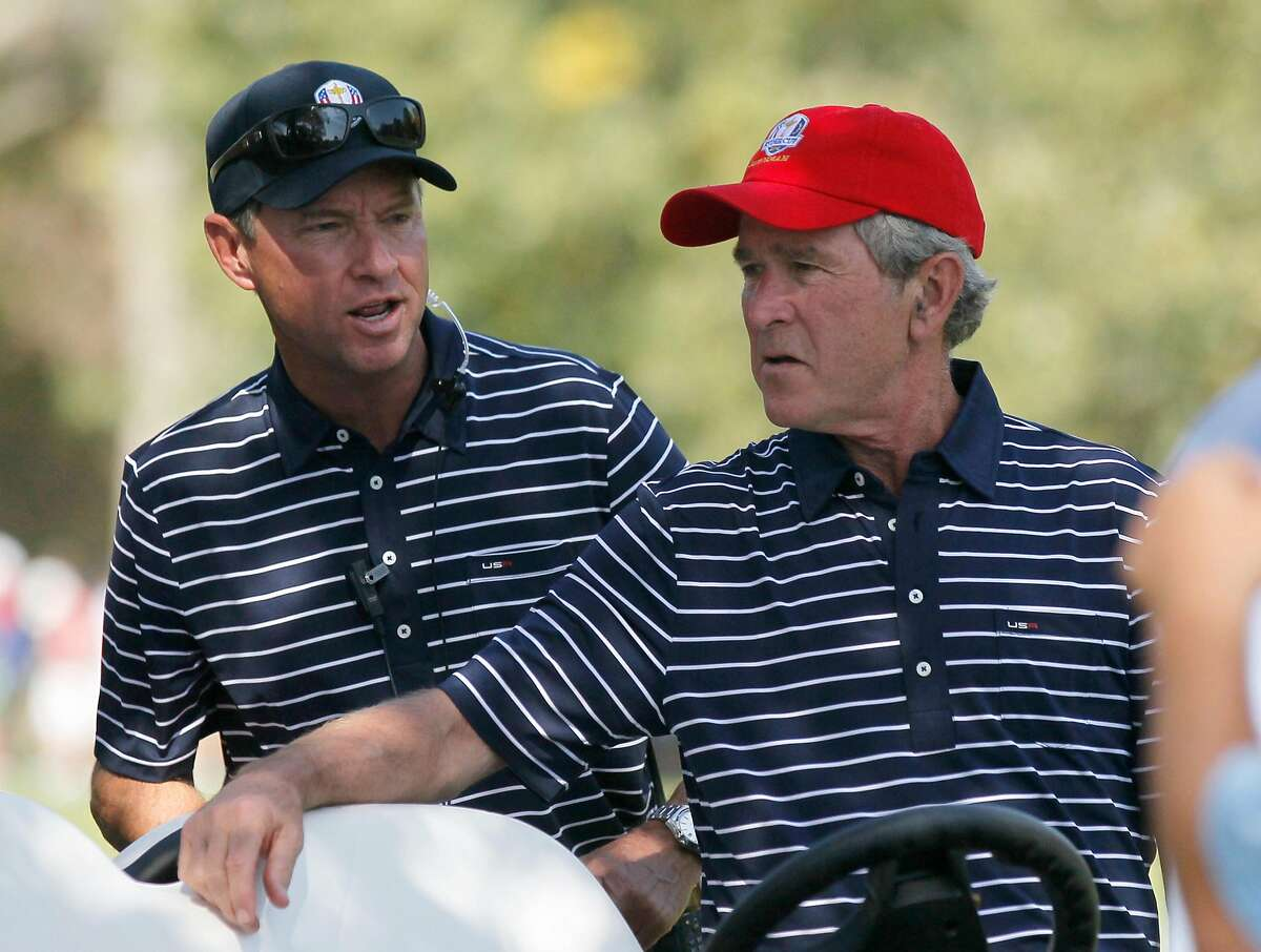 USA's captain Davis Love III talks to Former President George W. Bush during a four-ball match at the Ryder Cup PGA golf tournament Saturday, Sept. 29, 2012, at the Medinah Country Club in Medinah, Ill. (AP Photo/Charles Rex Arbogast)
