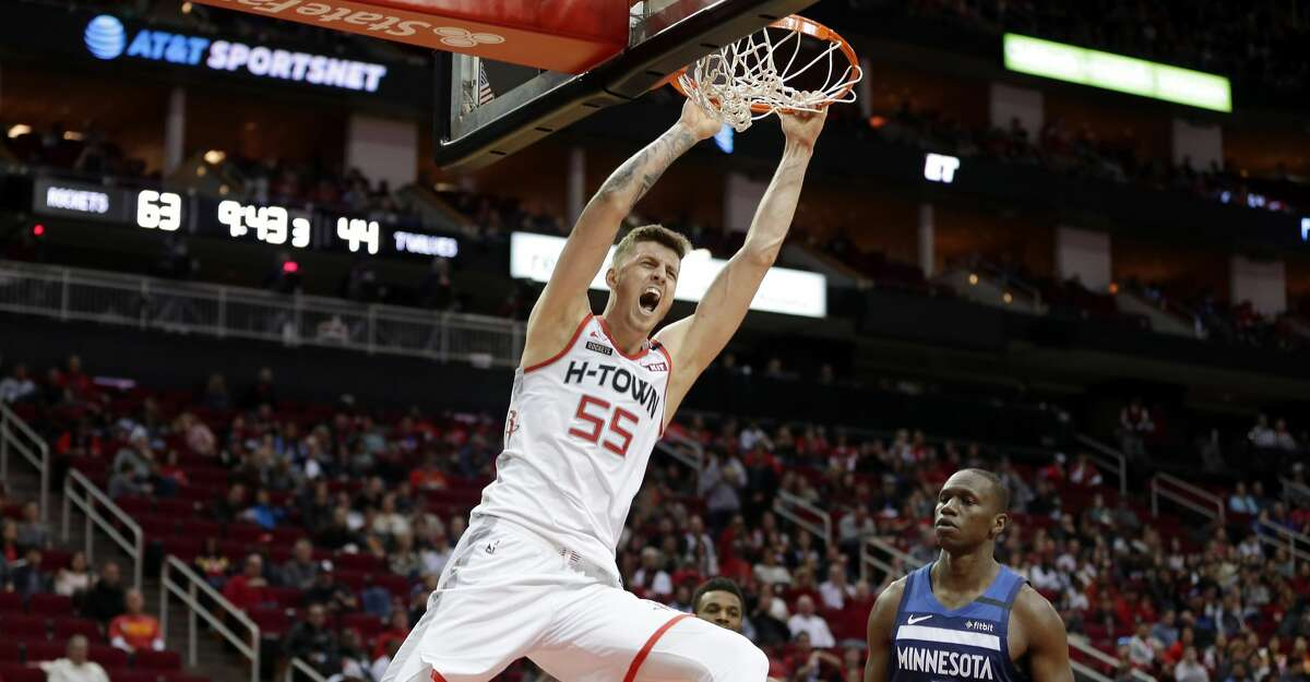Houston Rockets center Isaiah Hartenstein (55) hangs from the rim after dunking as Minnesota Timberwolves center Gorgui Dieng (5) looks on during the second half of an NBA basketball game Saturday, Jan. 11, 2020, in Houston. (AP Photo/Michael Wyke)
