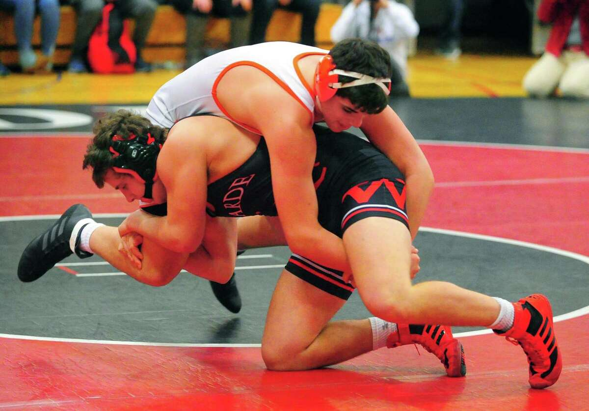 Fairfield Warde's Griffin Gallati, facing left, and Danbury's Sean Donovan try to topple each other on Tuesday.