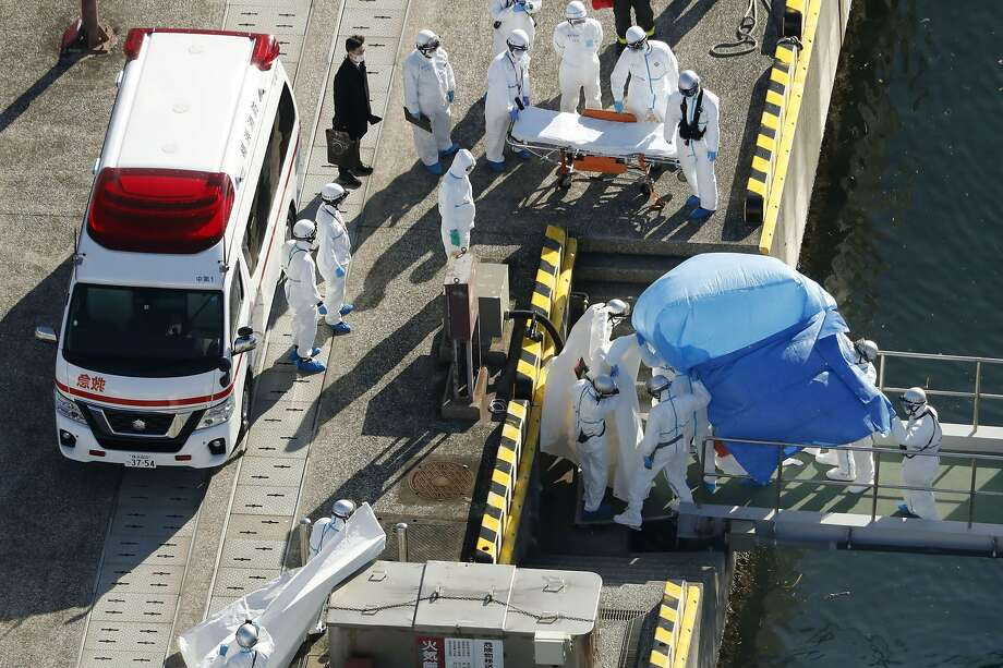 Medical workers in protective suits lead a passenger tested positive for a new coronavirus from the cruise ship Diamond Princess at Yokohama Port in Yokohama, south of Tokyo, Wednesday, Feb. 5, 2020. Japan said Wednesday 10 people on the cruise ship have tested positive for the new virus and were being taken to hospitals. Health Minister Nobukatsu Kato said all the 3,700 people and passengers on the ship will be quarantined on board for up to 14 days under Japanese law. (Hiroko Harima/Kyodo News via AP) Photo: Hiroko Harima, Associated Press