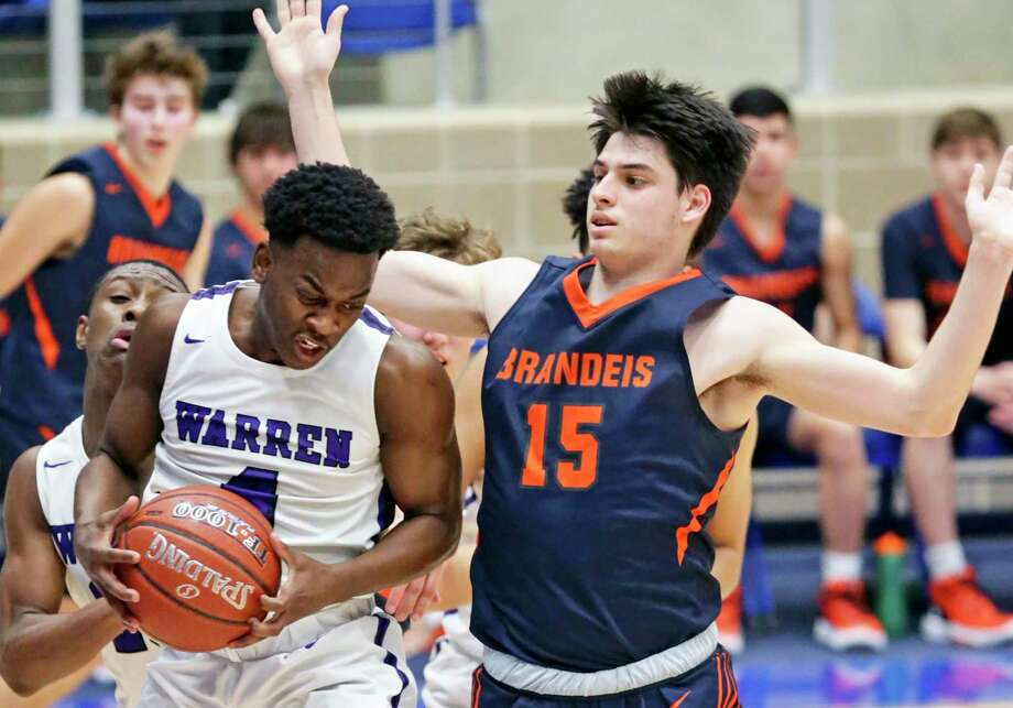 Warrior guard Zane Elmore rips a defensive rebound down in front of Andrew Lazinbat as Brandeis plays Warren in boys basketball at Northside Gym on Feb. 3, 2020. Photo: Tom Reel, San Antonio Express-News / Staff Photographer / **MANDATORY CREDIT FOR PHOTOG AND  SAN ANTONIO EXPRESS-NEWS/NO SALES/MAGS OUT/TV