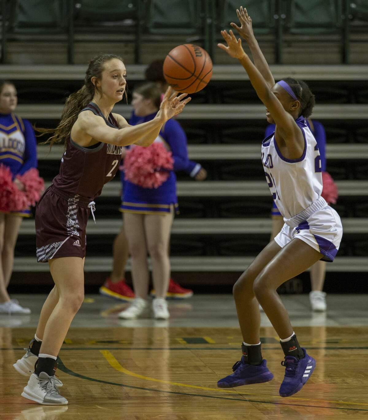 Lee's Maggie Erdwurm passes the ball as Midland High's Ahmaria Tennon guards her Tuesday, Feb. 4, 2020 at Chaparral Center.