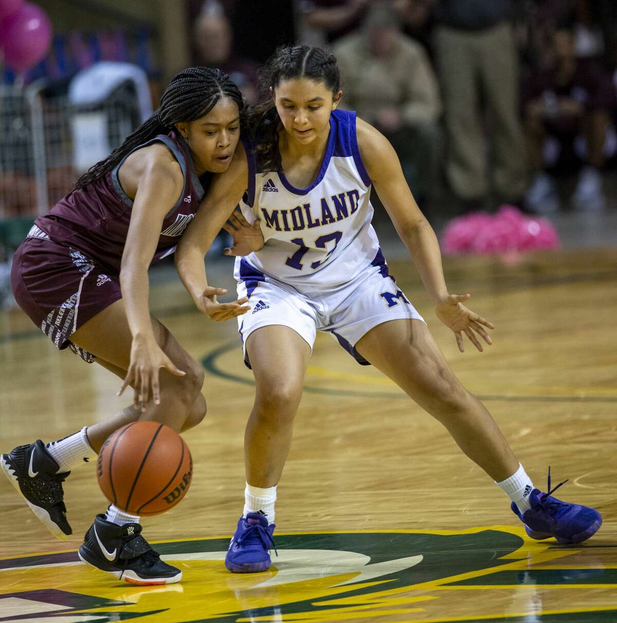 Midland High's Noemi Arciga attempts to steal the ball from Lee's Sa'Nya Green on Tuesday, Feb. 4, 2020 at Chaparral Center.