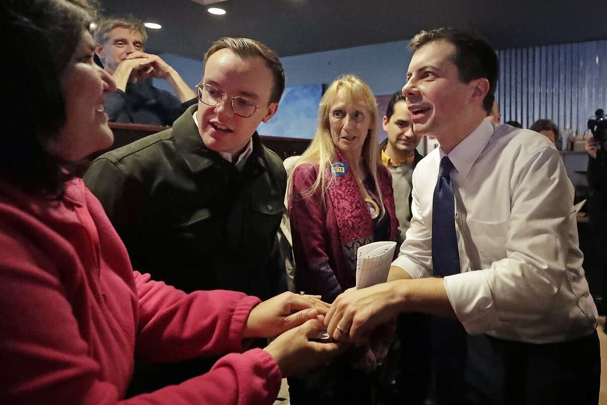 Democratic presidential candidate former South Bend Mayor Pete Buttigieg, right, and his husband, Chasten Buttigieg, left, greet people at a campaign event, Tuesday, Feb. 4, 2020, in Hampton, N.H. (AP Photo/Elise Amendola)