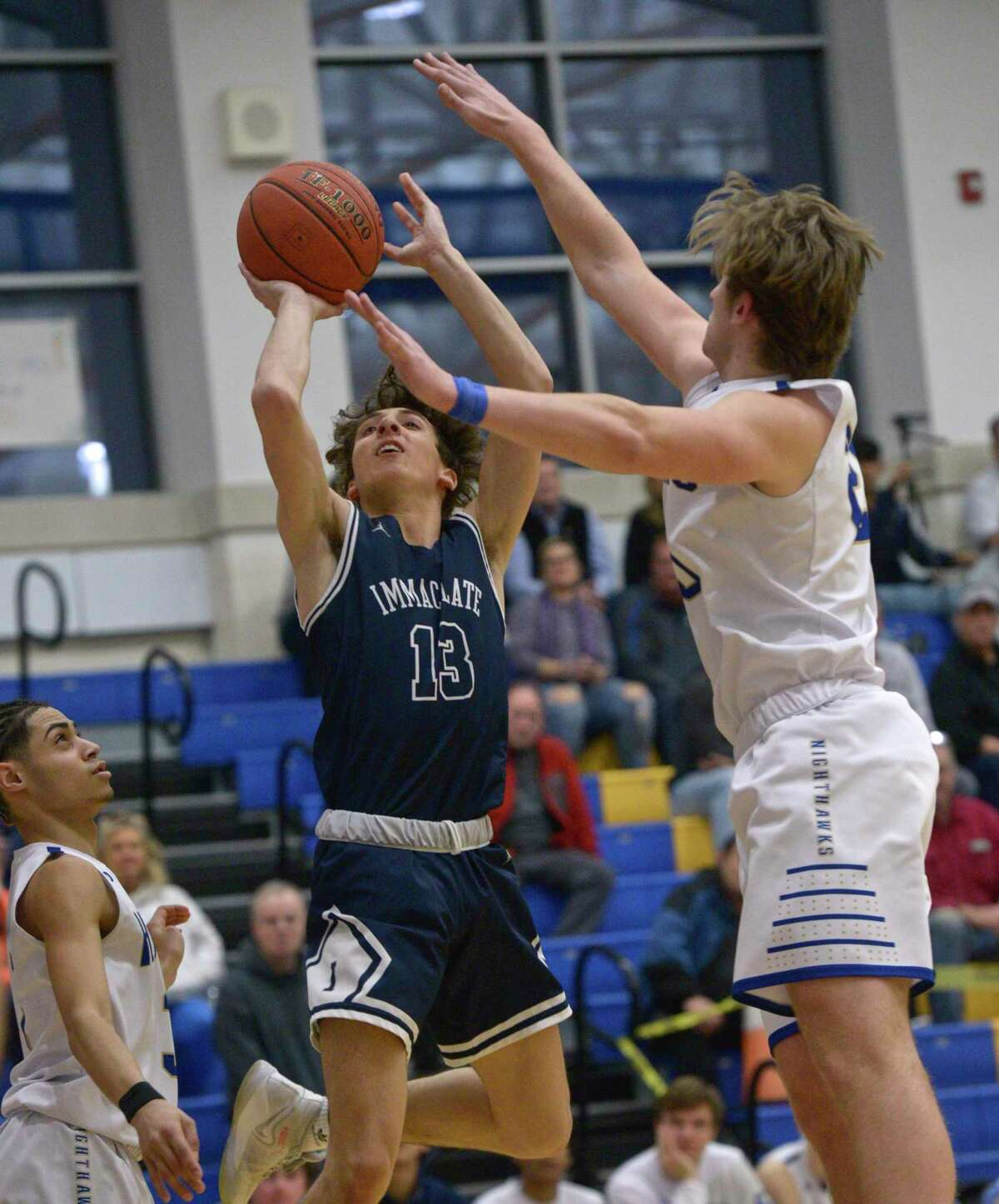 Immaculate's Sebastian Parenti (13) shoots over Newtown's Jack Mulligan (25) and Joseph McCray (3) during an SWC contest on Tuesday. No. 6 Immaculate defeated the Nighthawks, 54-53. For a complete recap and more photos, please visit GameTimeCT.com.
