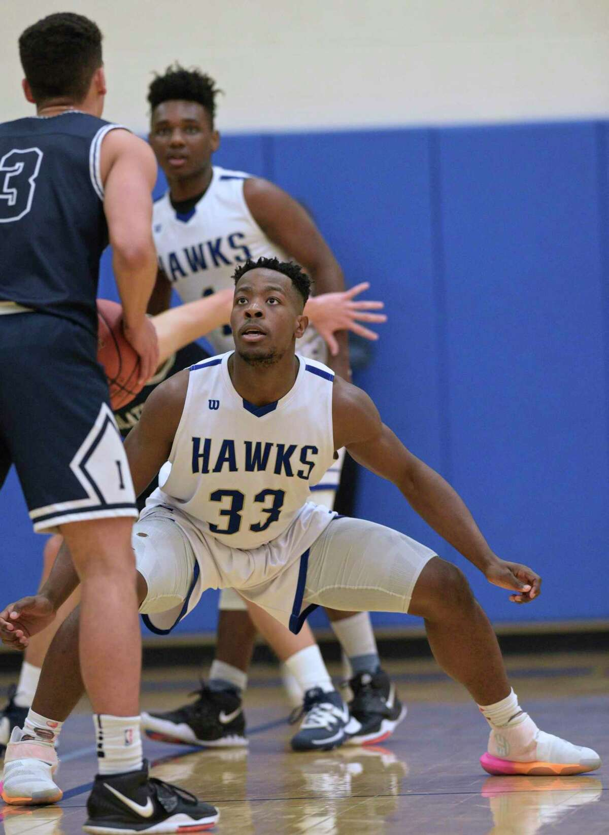 Newtown's Isaiah Williams (33) defends Immaculate's Diego Echavarria (3) in the boys basketball game between Immaculate and Newtown high schools, Tuesday night, February 4, 2020, at Newtown High School, in Newtown, Conn.