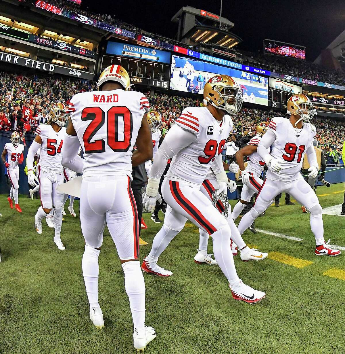 Arik Armstead #91, right, DeForest Buckner #99, center, Jimmie Ward #20, and the San Francisco 49ers run out of the tunnel during player introductions before the game against the Seattle Seahawks at CenturyLink Field on December 29, 2019 in Seattle, Washington. The San Francisco 49ers top the Seattle Seahawks 26-21. (Photo by Alika Jenner/Getty Images)
