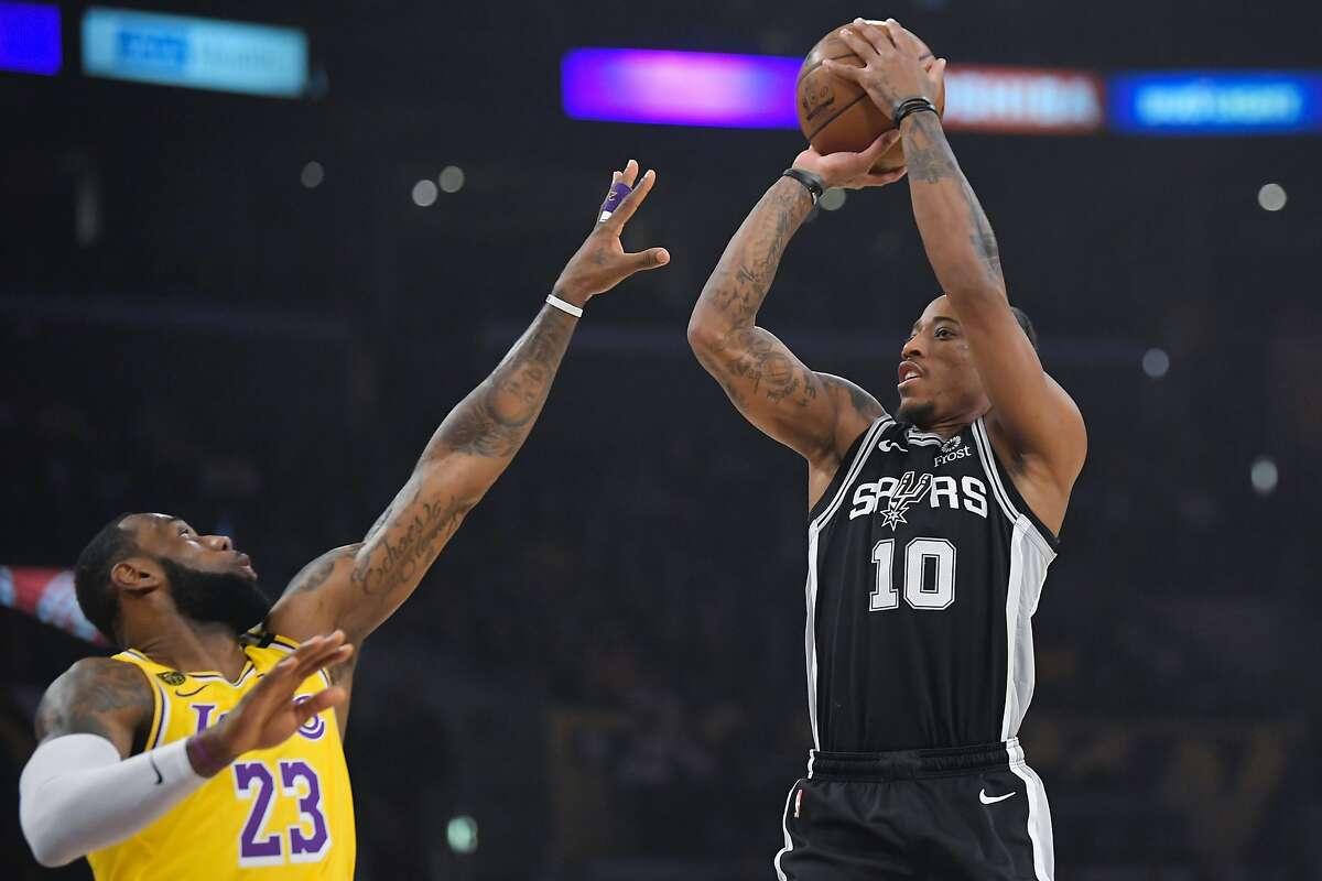 Spurs forward DeMar DeRozan shoots as Lakers forward LeBron James defends during an NBA game on Feb. 4, 2020.
