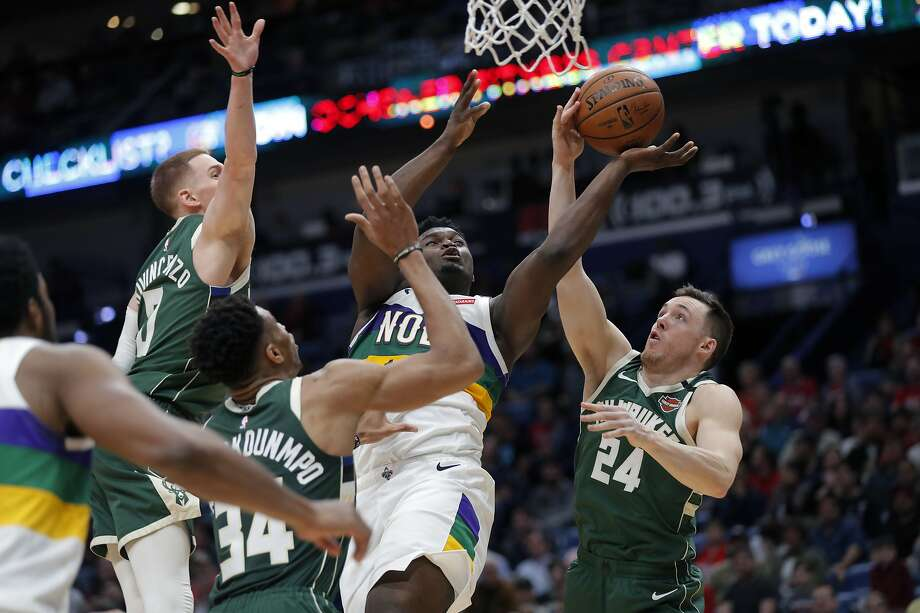 Pelicans rookie forward Zion Williamson (center) is fouled as he goes to the basket in the first half. Photo: Gerald Herbert / Associated Press