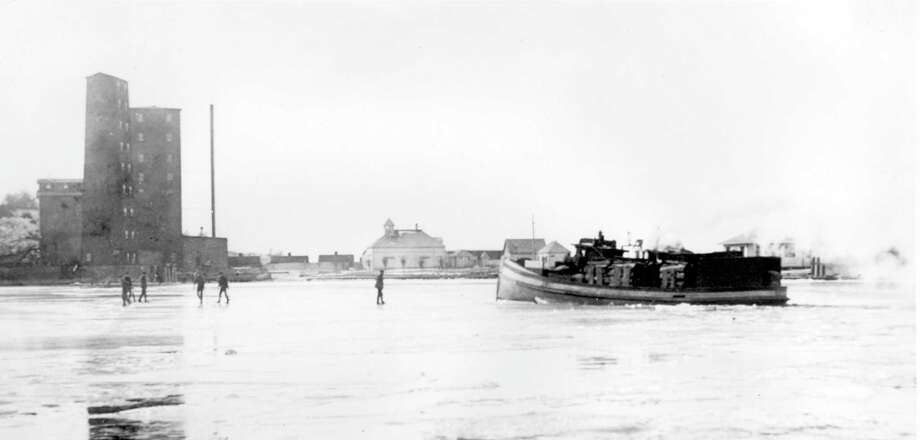 """Ice skaters on Betsie Bay in 1906 with Fairchild's fishtug """"Maggie Lutz"""". South Frankfort grain elevator and life saving station is in background. (Courtesy photo/Benzie Area Historical Society)"""