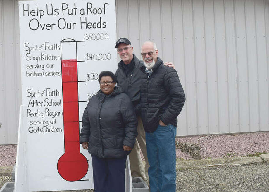 Spirit of Faith program director Polly Pulley (from left), Alan Bradish and Dennis Doyle stand in front of a fundraising sign that shows the progress toward raising $50,000 to replace the roof at the Spirit of Faith soup kitchen. Photo: Rochelle Eiselt | Journal-Courier