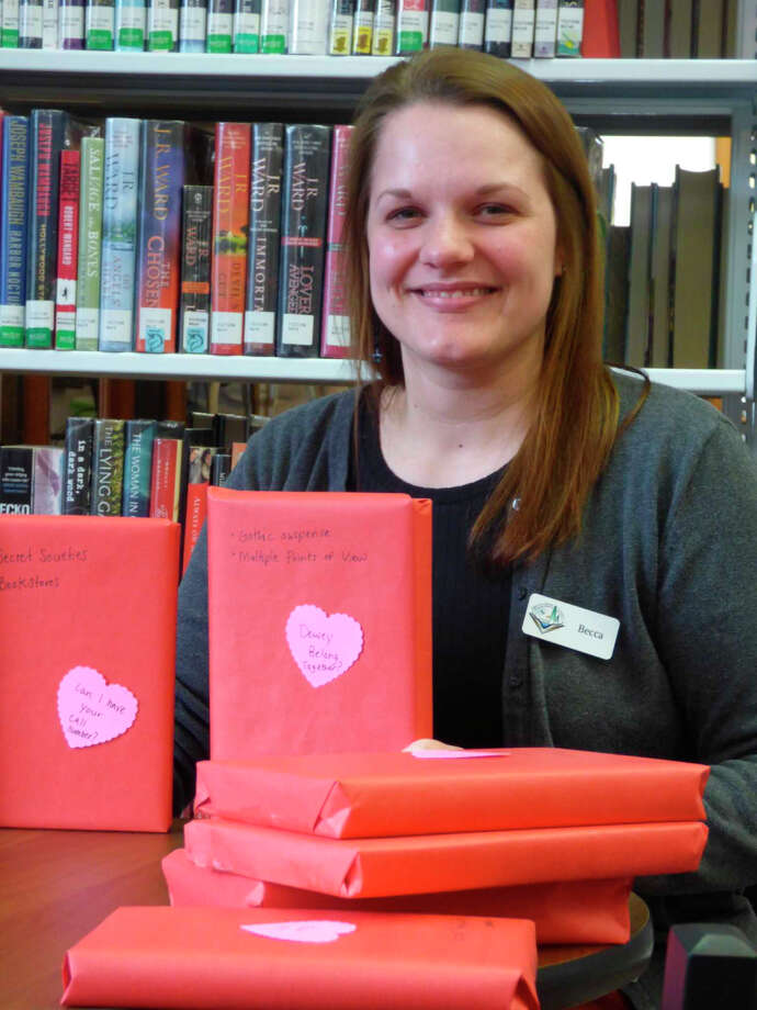 """Librarian Becca Brown poses with books wrapped in preparation for the library's """"Blind Date with a Book"""" program which starts Feb. 7. Photo: Scott Fraley/News Advocate"""