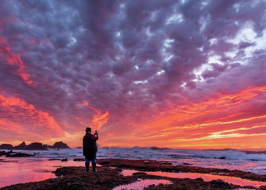 Alison Young photographs a brilliant sunset just after low tide at Pillar Point about 15 miles south of San Francisco. The rocks of Pillar Point jut out into the Pacific Ocean toward the left. The Mavericks surfing competition takes place in the waves toward the right when winter storms create enormous swells. Photo: CBSI/CNET