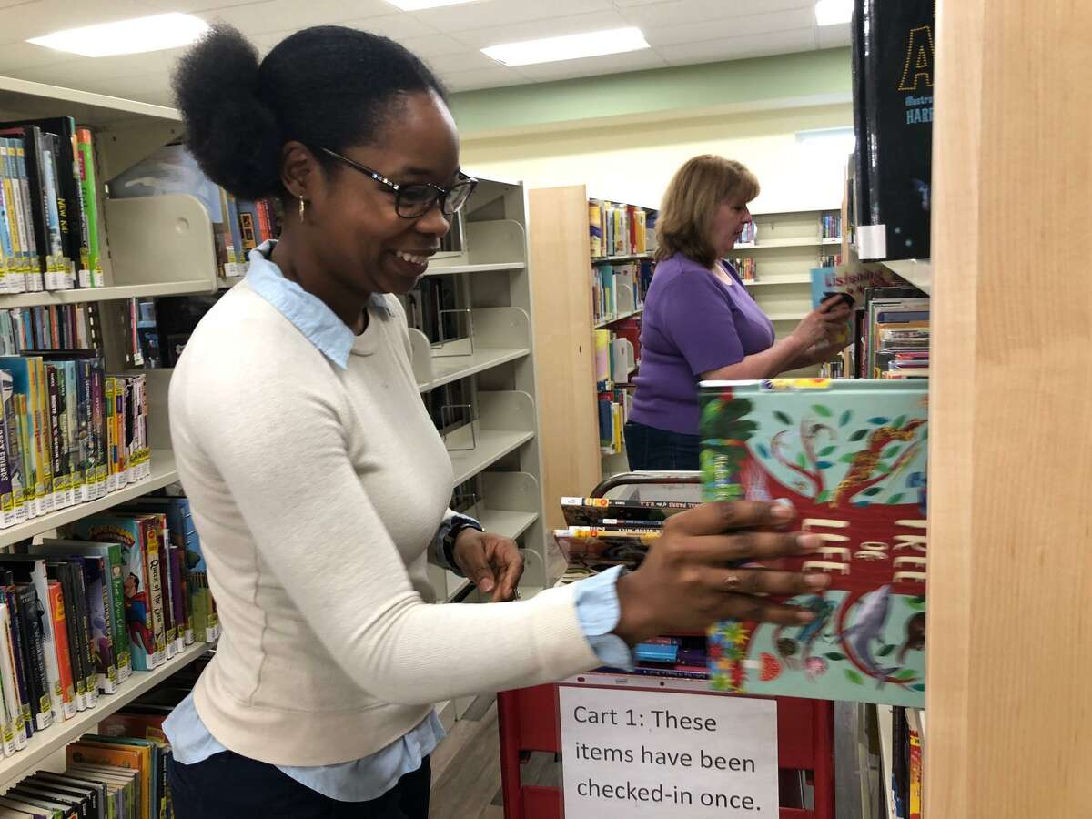 Plumb Memorial Library staffers Whitney Lee, front, and Debbie Semonich stack books on shelves in the newly renovated children's department.