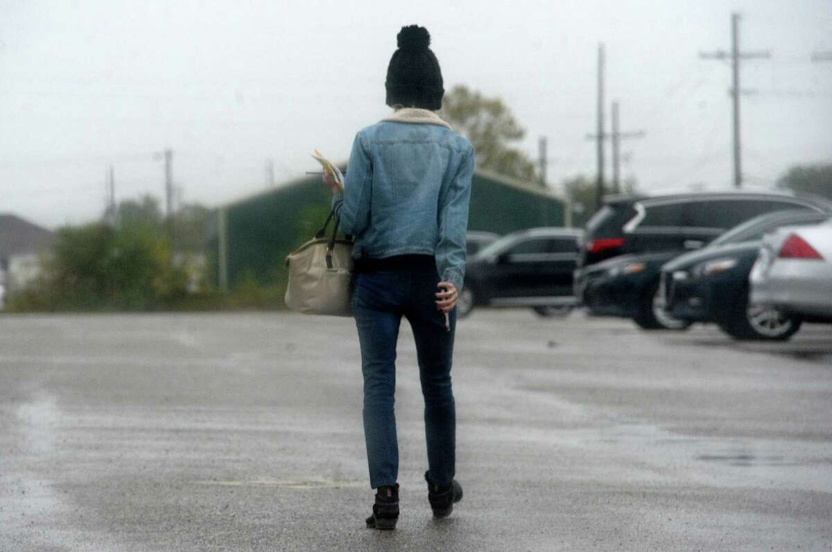 A woman dressed for the cooler temperatures to come makes her way through downtown Beaumont as showers move in Thursday. Temperatures will begin to fall, with a blast of cold weather expected to move into the region by next week. Photo taken Thursday, November 7, 2019 Kim Brent/The Enterprise