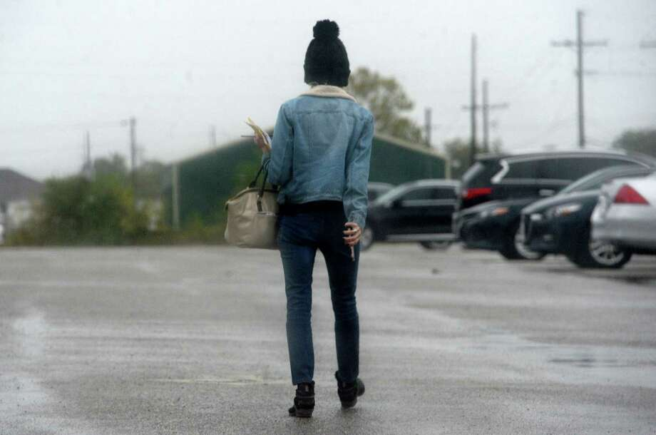 A woman dressed for the cooler temperatures to come makes her way through downtown Beaumont as showers move in Thursday. Temperatures will begin to fall, with a blast of cold weather expected to move into the region by next week. Photo taken Thursday, November 7, 2019 Kim Brent/The Enterprise Photo: Kim Brent / The Enterprise / BEN