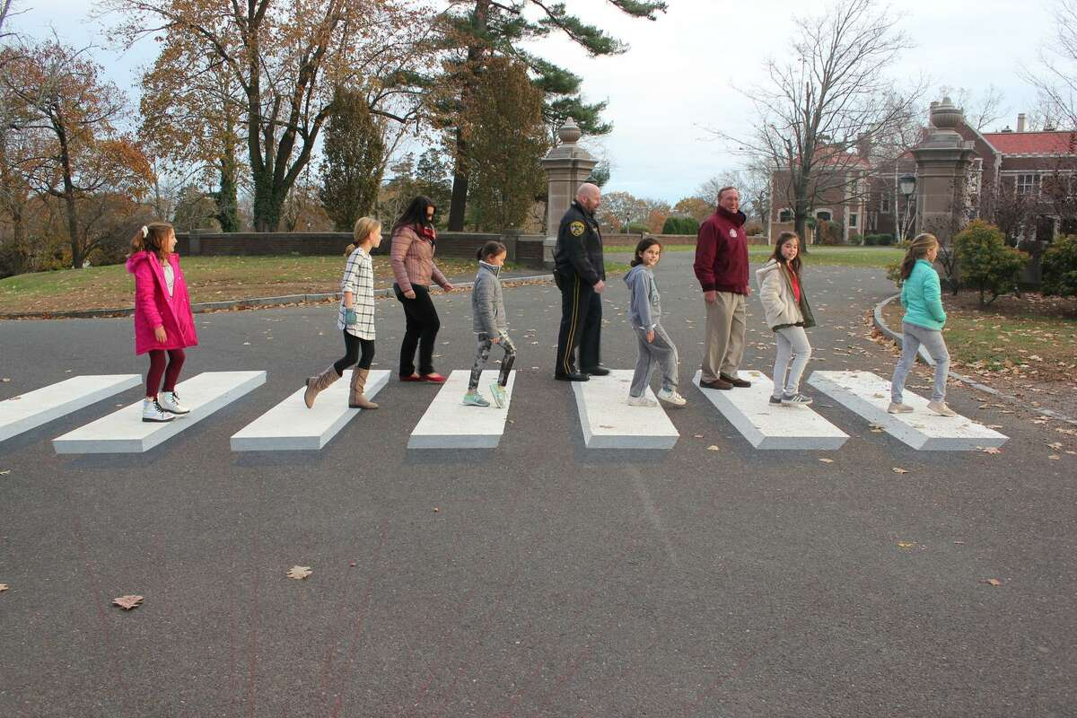 """Girl Scouts and supporters of their efforts to install a 3D crosswalk in Waveny Park do their best impression of The Beatles """"Abbey Road"""" cover. In front are Girl Scouts Kathryn Iacono, Stella Heijens, Madison Ruggieri, Treasure Hudson, Kate Beuerlein and Ella Ferrer. In back are Maria Coplit, Deputy Police Chief John DiFederico and Recreation Director Steve Benko."""