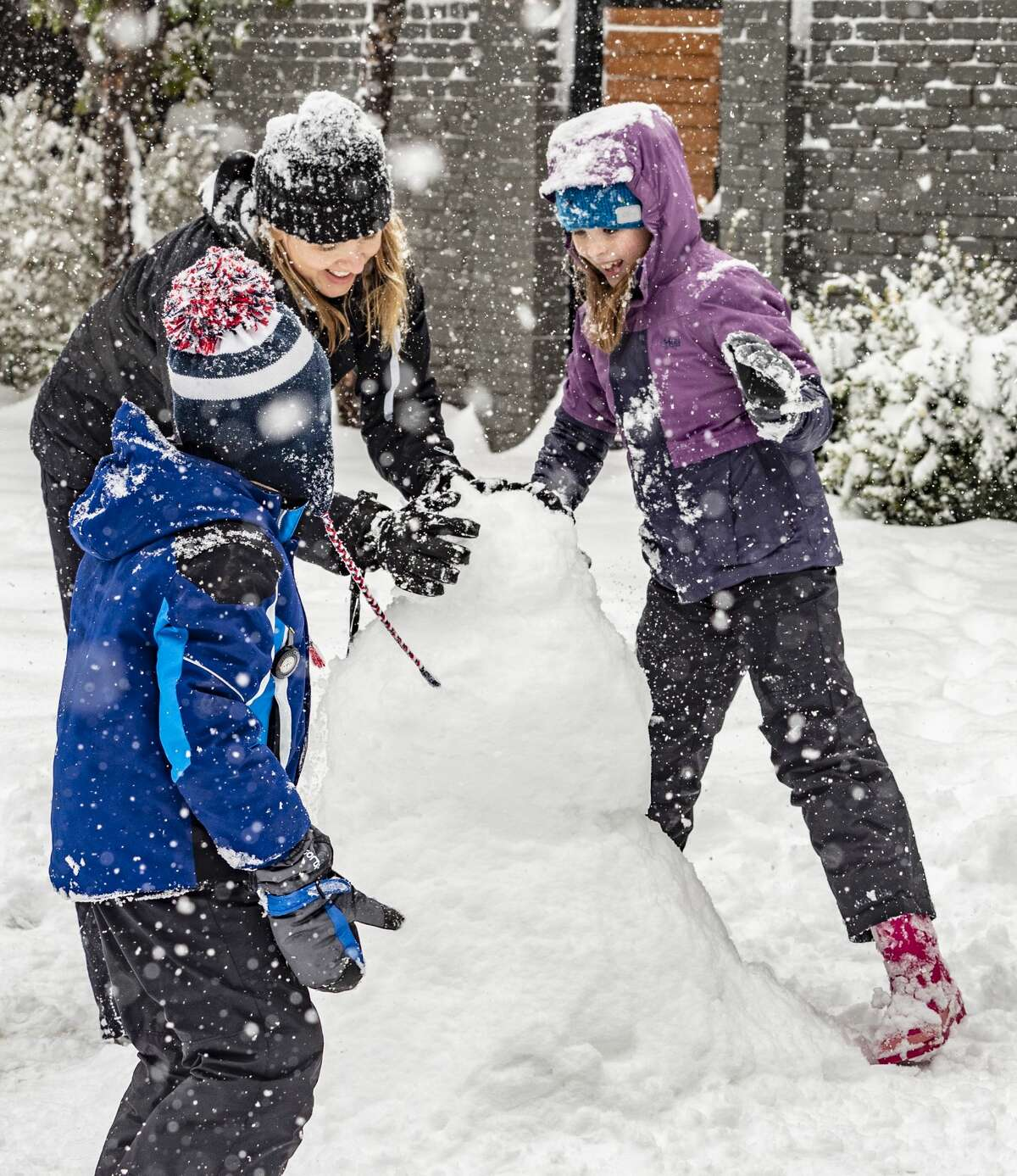 Jennifer Sell and her children, Caroline and Griffin, work on making a snowman 02/05/2020 as they enjoy a snow-day off from school. Tim Fischer/Reporter-Telegram >>>See more photos of snowfall across Midland and West Texas on Feb.5, 2020...