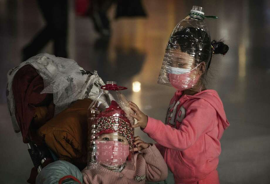 Children at Beijing Capital International Airport last month wear makeshift protection and face masks.  A reader wonders why people don't take such precautions with the flu, which kills thousands every year. Photo: Kevin Frayer / Getty Images / 2020 Getty Images