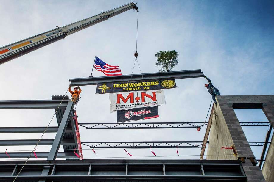 Ironworkers place the last steel beam on the Delta College Downtown Midland Center during a topping out ceremony Wednesday at 419 E. Ellsworth St. (Katy Kildee/kkildee@mdn.net)