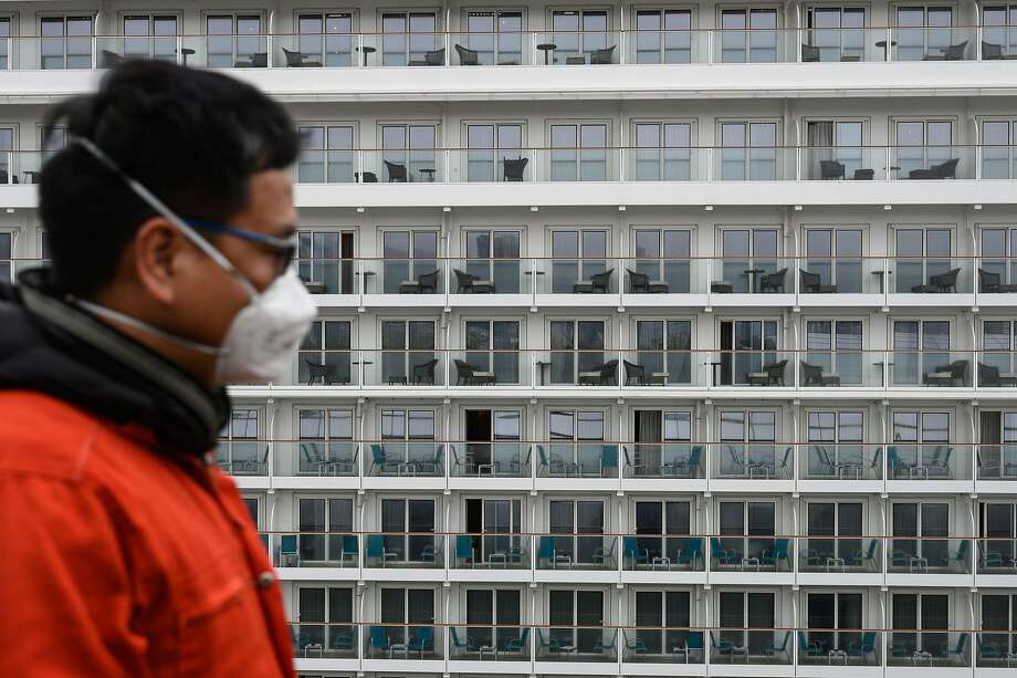 A health worker looks at a cruise ship in Hong Kong harbor about to be inspected for the SARS-like virus. Photo: Philip Fong / AFP Via Getty Images