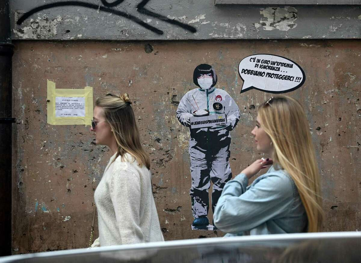 """Two women walk by a mural painting reading """"There's an epidemic of ignorance in the air, we must protect ourselves!"""" referring to the coronavirus outbreak by the street artist Laika near the Chinese district in Rome, on February 4, 2020."""