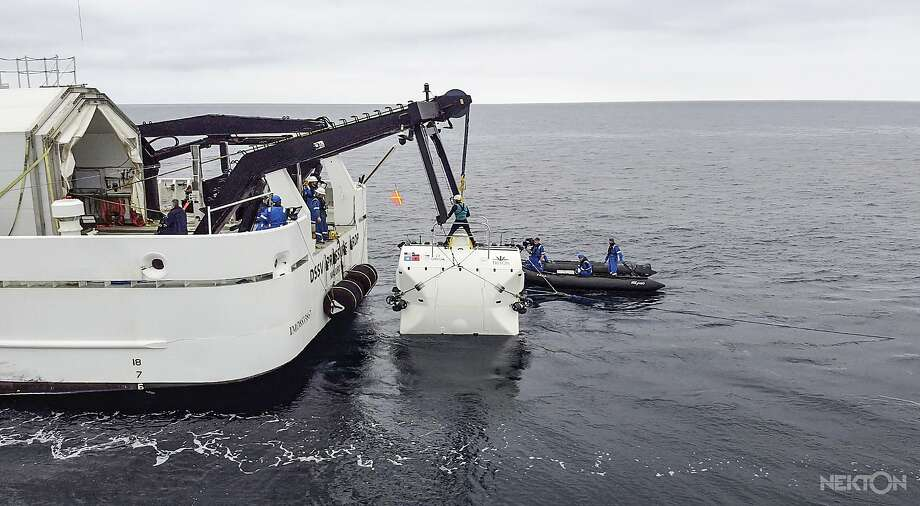 Scientists lower a submarine that can dive to almost 36,000 feet down — deeper than Mount Everest is tall. The two-person crew compartment is wrapped in a 3.5-inch titanium cocoon. Photo: Nekton