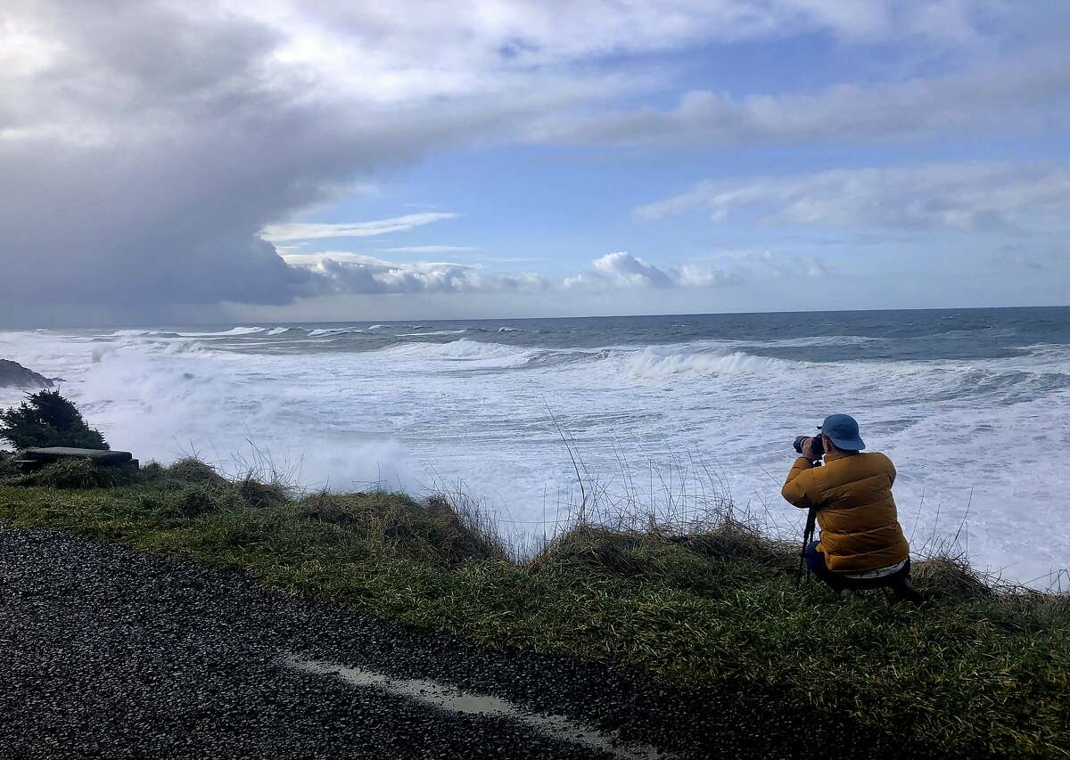 In this Jan. 11, 2020 photo a man photographs waves crashing onto the cliffs at Rodea Point in Lincoln County, Ore. during an extreme high tide that coincided with a big winter storm. Amateur scientists are whipping out their smartphones to document the effects of extreme high tides on shore lines from the United States to New Zealand, and by doing so are helping better predict what rising sea levels due to climate change will mean for coastal communities around the world. (AP Photo/Gillian Flaccus)